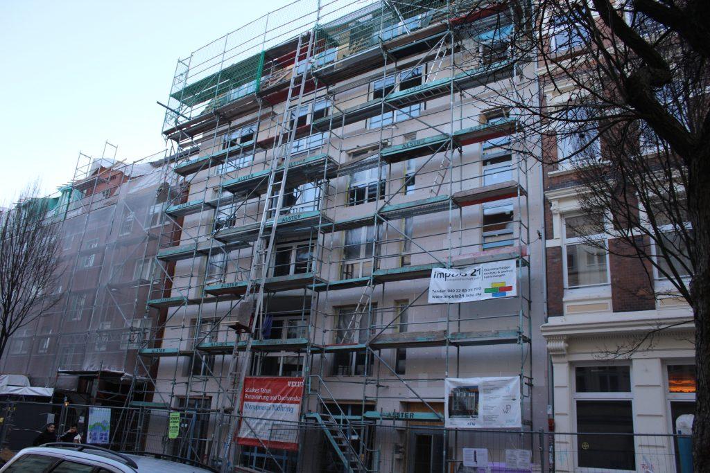 Das Gebäude ist hinter einem Gerüst zu sehen, es hat 5 Stockwerke. Die Fenster sind eingesetzt