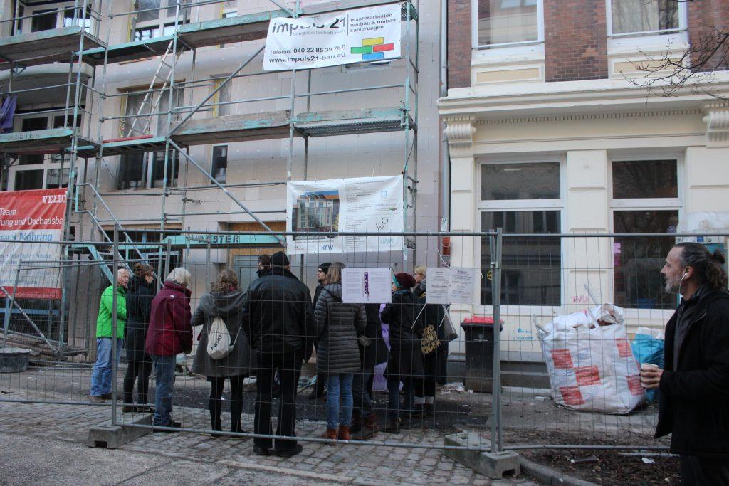 Eine Gruppe Menschen stehen hinter einem Bauzaun vor dem Rialto