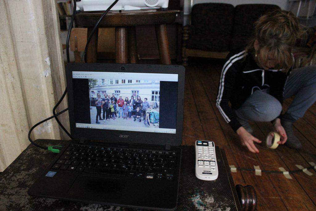 Jemand klebt kniend ein Kabel auf den Boden während ein Laptop ein Gruppenfoto zeigt