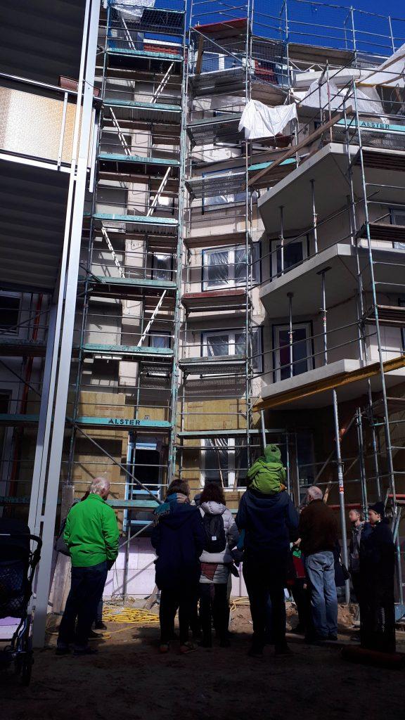 Eine Gruppe Menschen stehen auf einer Baustelle. Im Hintergrund ist eine Häuserwand, an der ein Baugerüst steht.