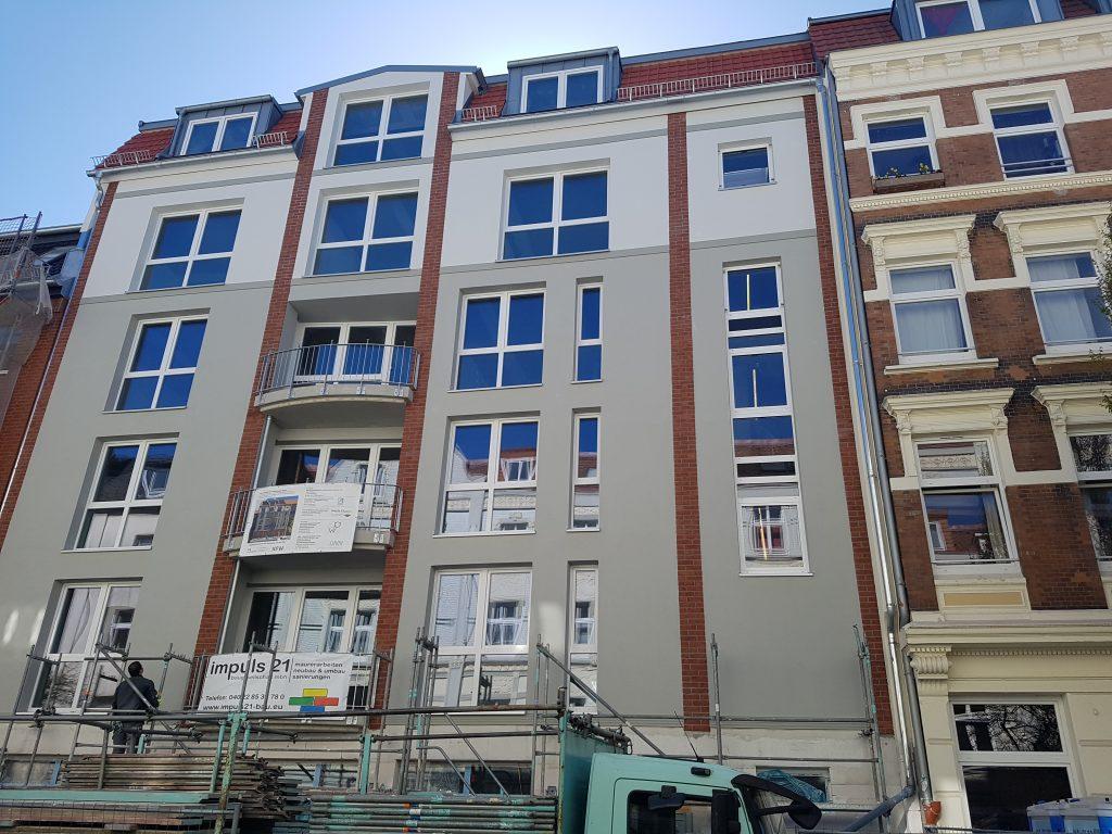 Die Fassade ist zu sehen: Oben helles, unten dunkleres Grau mit vertikalen Riemchen. Unten im Bild Reste des Gerüsts und ein LKW beladen mit Gerüstteilen.