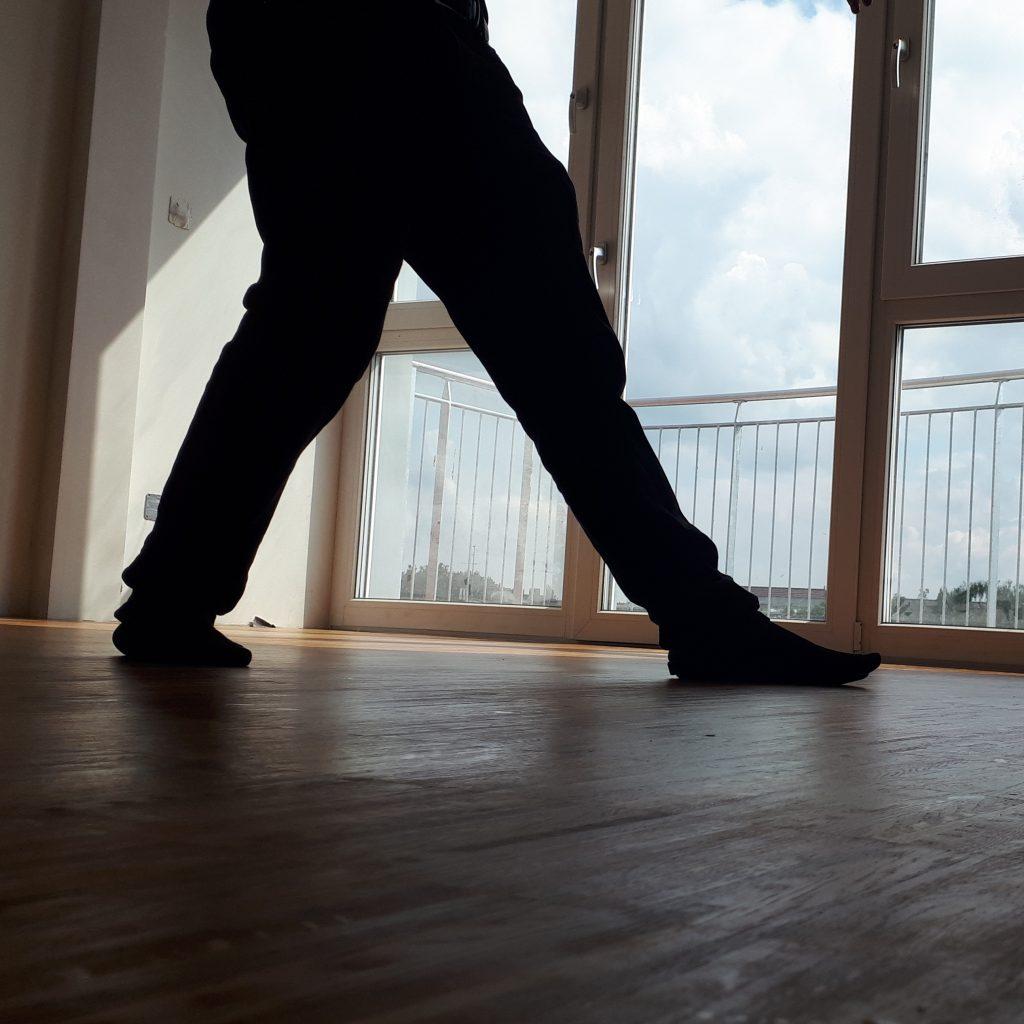 Im Gegenlicht der Balkontür und -fenster ist ein Paar Beine in Socken auf Holzfußboden zu sehen.
